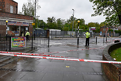 © Licensed to London News Pictures. 02/05/2018. LONDON, UK.  A police cordon surrounds the scene of a shooting in Queensbury, north west London.  A man was fatally shot and another injured following the shooting in Cumberland Road adjacent to Queenbury tube station.  It is reported that one of the victims staggered into a minicab office (pictured left).  Photo credit: Stephen Chung/LNP