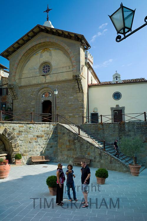 Tourists by Tuscan Church of San Niccolo, Chiesa San Niccolo, in Piazza Francesco Ferrucci in Radda-in-Chianti, Tuscany, Italy