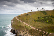 A family of ramblers passes along the South West Coast Path beneath Anvil Point Lighthouse near Swanage, Dorset, UK