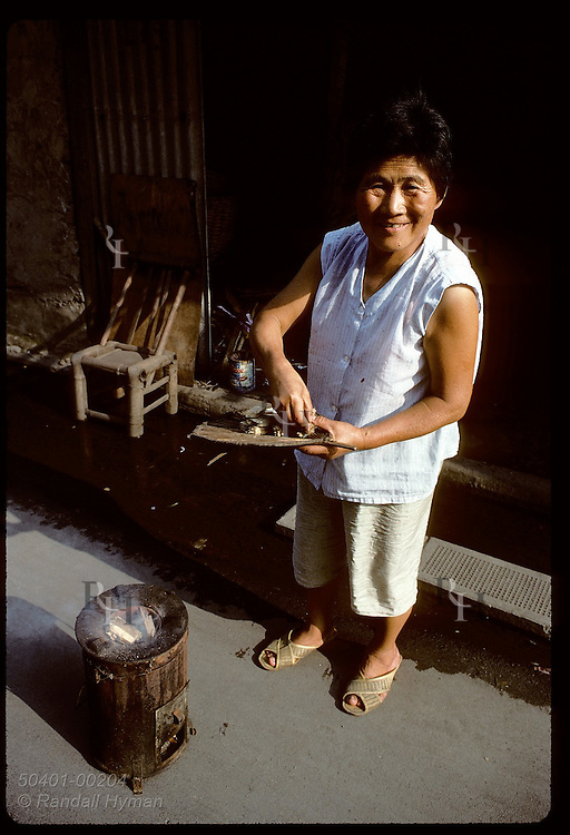 Woman uses wood in cooking stove outside her humble bamboo shack in industrial area of Shanghai. China