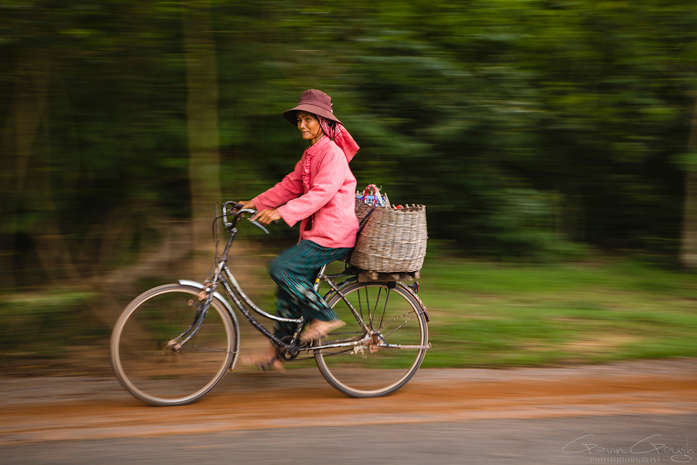 A Cambodian woman in a pink jacket cycling along a road in the woods outside the temple complex, Angkor Wat, Siem Reap, Cambodia