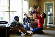 Melinda Townsend-Breslin, from right, holds up her five-month-old son, Emory, while her father, John Townsend, and husband, John Breslin looks on in her father's home in Louisville, Ky. on Sunday March 22, 2015. Mary Townsend never got to see her grandson after loosing her fight to pancreatic cancer when she was 58. <br /> <br /> Photos by William DeShazer
