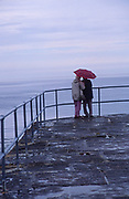 AE2KY9 Elderly couple with umbrella in rainy weather looking out to sea from the end of a pier