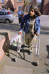 Teenage girl with physical disability holding bag of shopping and walking with frame,