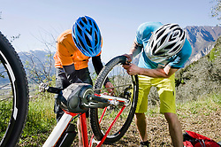 Two Mountainbikers repairing flat type on E-bike