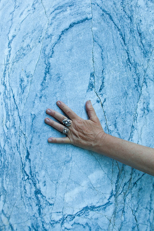 Liana Welty places her hand against a clean slab of marble granite in the Crystalline Hills, Wrangell-St. Elias National Park, Alaska.