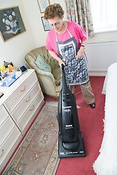 Older woman hoovering in the bedroom,