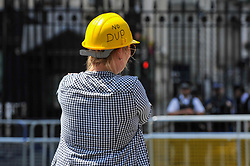 "© Licensed to London News Pictures. 21/06/2017. London, UK. A woman wears a hard hat with the text ""No DUP"" as Anti-Tory protesters stage a ""dance off"" outside Downing Street following the Queen's Speech in Parliament. Photo credit : Stephen Chung/LNP"