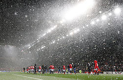 Both teams walk out into a snow storm before the Emirates FA Cup, quarter final match at Old Trafford, Manchester.