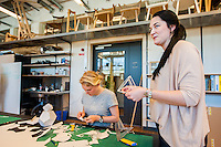 Final-year furniture design students in their working spaces.