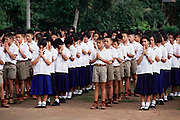 Jeeraporn Khuankaew's schoolmates line up outside on the athletic field each morning before class to observe the raising of the flag, the recitation of a prayer and to listen to the pricipal talk and talk. A few of the boys were singled out for having hair that was too long and they had their hair cropped very short on the spot. (From Peter Menzel's Material World Project that showed 30 statistically average families in 30 countries with all their possessions)