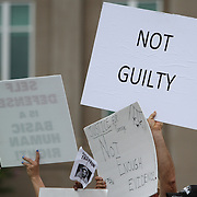 A George Zimmerman supporter holds up a not guilty sign in the protest area, prior to the trial of George Zimmerman at the Seminole County Courthouse, Saturday, July 13, 2013, in Sanford, Fla. Zimmerman had been charged for the 2012 shooting death of Trayvon Martin. (AP Photo/Alex Menendez)