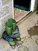 A hill farmer's wellies and waterproofs outside the farmhouse door, Bransdale, North York Moors, North Yorkshire, UK