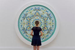 """© Licensed to London News Pictures. 23/06/2017. London, UK. A staff member views """"Contemplation"""", 2007, by Damien Hirst (estimate GBP0.7-0.9m) at the preview of Sotheby's Contemporary Art Sale in New Bond Street.  The auction, which is dominated by Pop art, takes place on 28 June. Photo credit : Stephen Chung/LNP"""