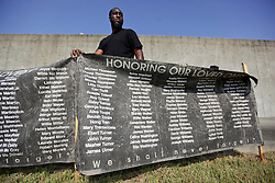 29 August 2015. Lower 9th Ward, New Orleans, Louisiana.<br /> Hurricane Katrina 10th anniversary memorial.<br /> Luther Adamson stands with the banners containing the names of hurricane Katrina victims at the point in the levee which gave way a decade ago. <br /> Photo credit©; Charlie Varley/varleypix.com.