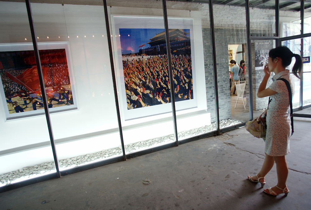 A woman photograph of a scene from the cultural revolution in Dazhanzi at Photogallery 798. China's art scene is becoming popular among foreign art collectors pushing prices higher.