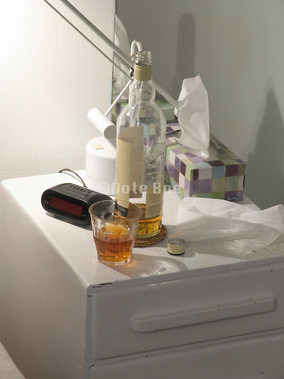 open whisky bottle with glass on a night stand