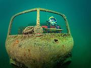 Kirby Morgan Superlite 17 commercial diver behind the army truck wheel at Dutch Springs, Scuba Diving Resort in Bethlehem, Pennsylvania