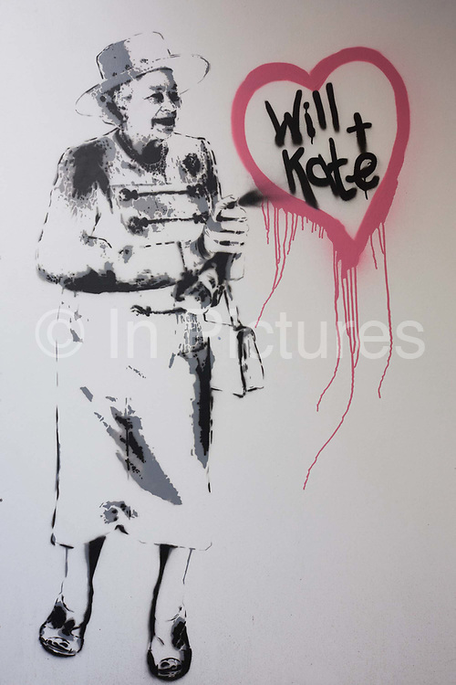 Royal wedding graffiti shows the Queen using an aerosol to spray Prince William and Kate Middleton in a heart. Seen ion a street in central London, it is not known if the author of the artwork is Banksy, the subversive, underground and anonymous street artist or another wannabe or copycat. In the weeks before the royal wedding event gripped a largely negative public in terms of anti-royalism, the royal theme seemed to be everywhere, with flags and memorabilia on sale everywhere.