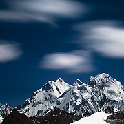 A telephoto view with motion blur of the clouds from Cuyoc Pass looking at the Peaks from tall right to left: Siulu Grande, Jurau, Sarapo in the Cordillera Huayhuash of the Andes Mountains in Peru.