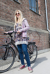 Teenage girl with bicycle against brick wall, Munich, Bavaria, Germany