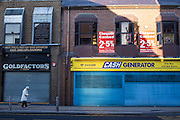 A British woman walks down the high street in Middlesborough town centre, North Yorkshire, United Kingdom.  She passes a Goldfactors and Cash Generator pawnbroker shops which are closed with their shutters down.