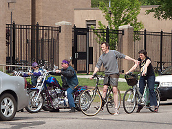 Two bicyclists sit at an intersection with two motorcyclists