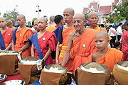 "Monks collecting alms at the That Luang festival, Vientiane, Lao PDR. Pha That Luang is the national symbol and most important religious monument of Laos. Vientiane's most important Theravada Buddhist festival, ""Boun That Luang"", is held here for three days during the full moon of the twelfth lunar month (November). Monks and laypeople from all over Laos congregate to celebrate the occasion with three days of religious ceremony followed by a week of festivities, day and night. The procession of laypeople begins at Wat Si Muang in the city centre and proceeds to Pha That Luang to make offerings to the monks in order to accumulate merit for rebirth into a better life. The religious part concludes as laypeople, carrying incense and candles as offerings, circumambulate Pha That Luang three times in honor of Buddha."