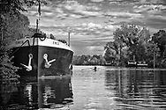 A rower from the local rowing club in le Port Marly, France makes his way past large ships moored along the shore.  Aspect Ratio 1w x 0.667h