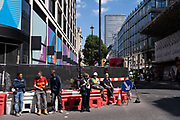 Workmen sitting in a line taking a break at a construction site along Oxford Street on 10th August 2021 in London, United Kingdom.