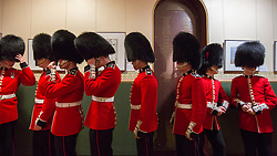 © Licensed to London News Pictures. 07/11/2015.  Royal Albert Hall, London, UK.  Members of the Coldstream Guards adjust their bear skins prior to the annual Festival of Remembrance.  Photo credit : Alison Baskerville/LNP