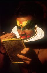Kathakali dancer putting on his makeup before performance,