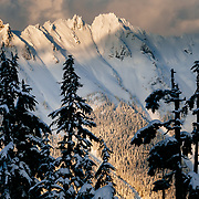 Mount Shuksan is illuminated by a clearing winter storm at sunset in North Cascades National Park, Washington.