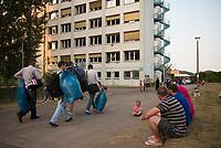 DEU, Deutschland, Germany, Berlin, 13.08.2015: Neueintreffende Füchtlinge tragen Müllsäcke mit ihrem Begrüßungsset (Kopfkissen, Bettwäsche, Handtücher) in der kurzfristig eingerichteten Notunterkunft im Berliner Stadtteil Karlshorst. Die vom DRK betriebene Erstaufnahmestelle in der Köpenicker Allee soll die Zentrale Aufnahmeeinrichtung für Asylbewerber der LaGeSo in Moabit entlasten.