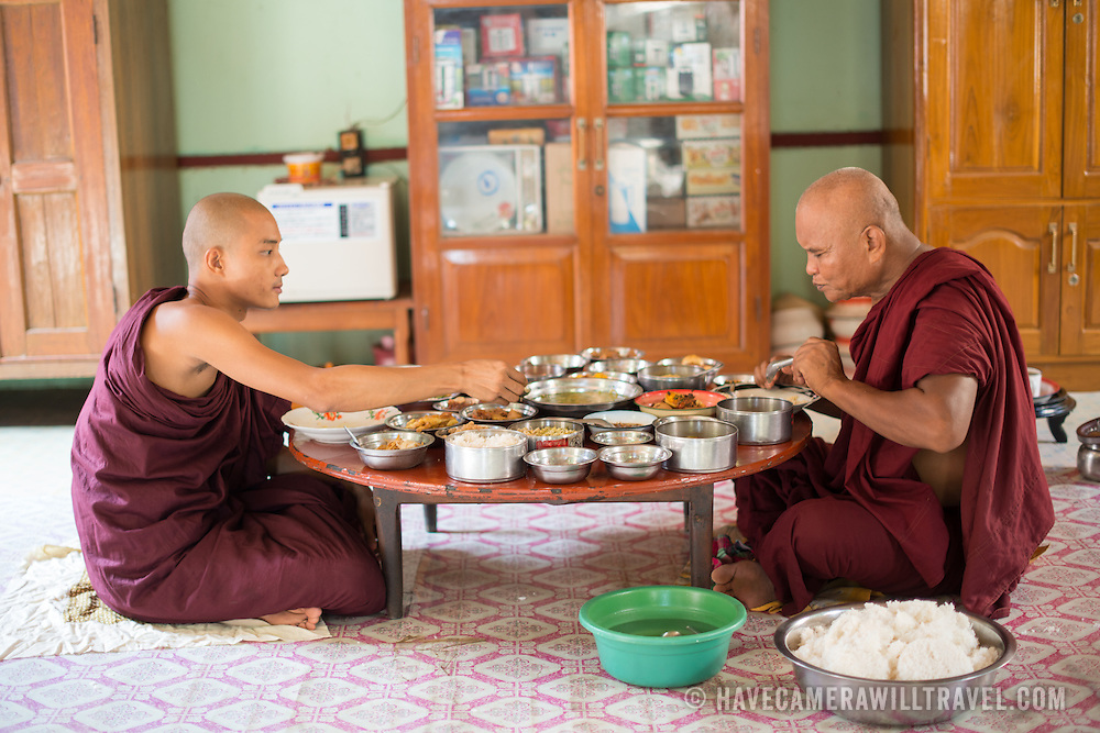 Two monks eating a midday meal at a Monastery in Bagan Myanmar (Burma).