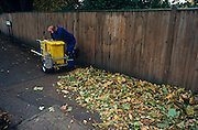 Resting road and leaf sweeper reads magazine on his cart during brief break of his morning shift in Dulwich, London.