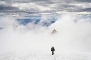 Kevin Steffa leads his climbing party across the Sulphide Glacier on Mount Shuksan, North Cascades National Park, Washington. Point 7935 emerges through the clouds.