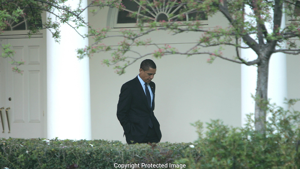 President Barack in deep thought as he walks down the colonade from the Oval Office to the White House residence before he boards Marine One on the first leg of his trip to London and the Economic Summit.  Photograph by Dennis Brack