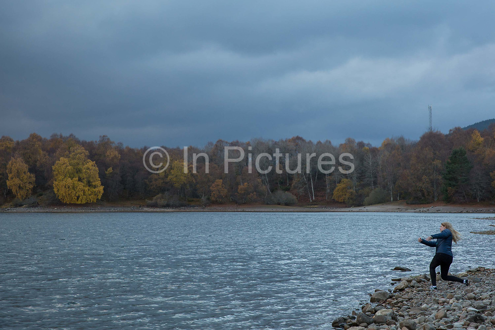 A woman skimming pebbles at Loch Vaa on the 6th November 2018 in Aveimore, Scotland in the United Kingdom. Behind the pinewoods, off the A95 between Aviemore and Boat of Garten is the lesser known Loch Vaa.