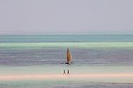 People walking on a sandbar and a sailing dhow.  Kiwendwa Beach, Zanzibar, Tanzania
