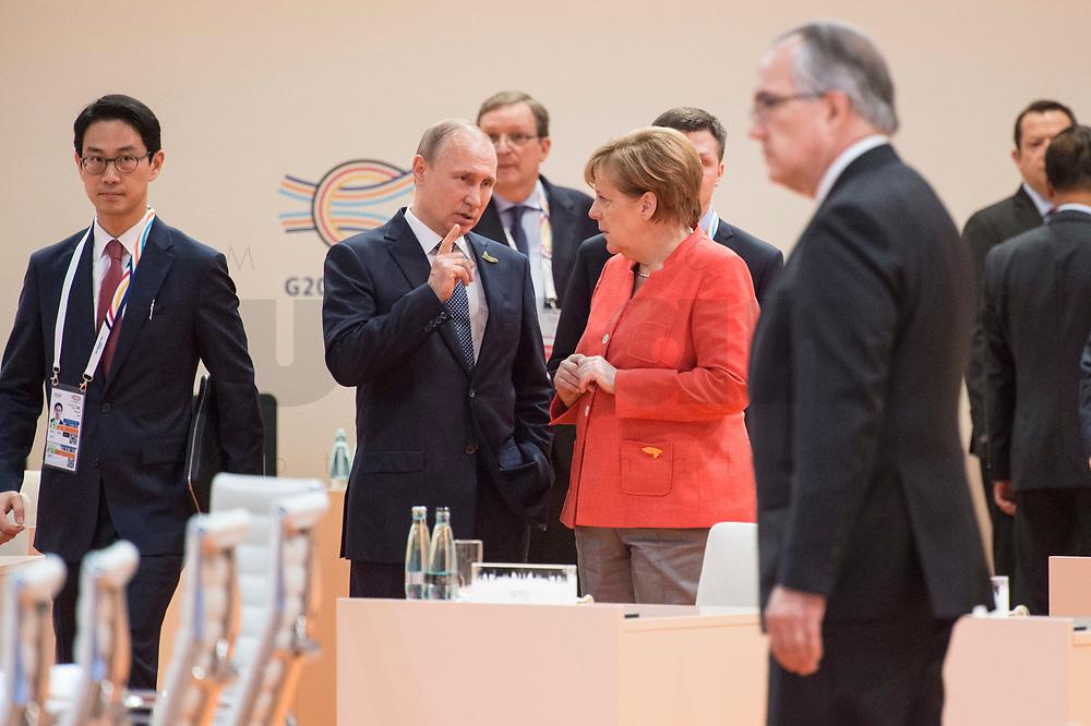 07 JUL 2017, HAMBURG/GERMANY:<br /> Vladimir Putin, Praesident Russische Foerderation, und Angela Merkel (R), CDU, Bundeskanzlerin, auf dem Weg durch den Sitzungssaal, 1. Arbeitssitzung, G20 Gipfel, Messe<br /> IMAGE: 20170707-01-006<br /> KEYWORDS: G20 Summit, Deutschland