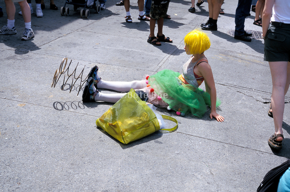 Funnily dressed girl with springs on her feet sitting in the middle of the sidewalk