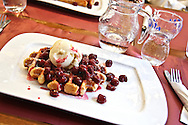 A Belgian waffle in the Liege style is served with cherries and ice cream at Brussels famous Dandoy cookie shop.