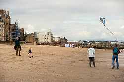We have all been there; trying to get a kite to fly to entertain the children.  Only once in the air the children lose interest.<br /> <br /> The weather was neither hot nor cold as Portobello residents took to the beach with plenty of social distancing possible. Kids, dogs and frogmen in the water all part of the easing of the lockdown scene.