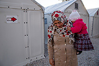 LEROS, GREECE - FEBRUARY 07: A refugee holds her young daughter outside their temporary shelter set up inside Leros refugee camp on February 07, 2015 in Leros, Greece. Hundreds of refugees are assisted by volunteers and Ngo's staff at the Leros refugee camp while waiting to board a ferry to travel to Athens. Photo: © Omar Havana. All Rights Are Reserved
