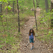 8 year old girl on a hike in the woods, wearing sandals and a hydration backpack.