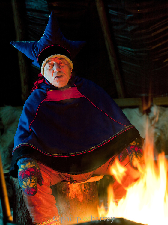 A Sami reindeer herder sits, chanting around the fire in his lavvu, a temporary home in Kirkeness, northern Norway