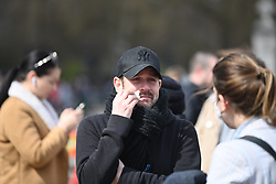 © Licensed to London News Pictures. 09/04/2021. London, UK. An emotional man wipes tears from his eyes at the gates outside Buckingham Palace. The British Royal Family have announced the death of Prince Philip, The Duke of Edinburgh, at the age of 99. Photo credit: Ben Cawthra/LNP