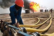 "Firefighters from the Kuwait Oil Company (called KWWK: Kuwait Wild Well Killers) connect hoses to water tanks and pumps by the second oil well fire they were working on in Iraq's Rumaila Oil field. Later in the day they failed to extinguish this fire with water and then tried to stop the flow of gas and oil with drilling mud using what is called a ""stinger,"" a tapered pipe on the end of a long steel boom controlled by a bulldozer. Drilling mud, under high pressure, is pumped through the stinger into the well, stopping the flow of oil and gas. This was also unsuccessful. The Rumaila field is one of Iraq's biggest oil fields with five billion barrels in reserve. Many of the wells are 10,000 feet deep and produce huge volumes of oil and gas under tremendous pressure, which makes capping them very difficult and dangerous. Rumaila is also spelled Rumeilah.."
