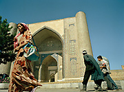 Uzbeks heading to the market, passing in front of Bibi-Khanym Mosque in the fabled city of Samarkand, on the ancient Silk Road. Uzbekistan.